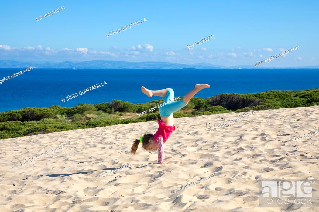 Stock Photo: four years old little girl doing gymnastics or handstand on sand dune of Valdevaqueros (Tarifa, Cadiz, Andalusia, Spain), with ocean and Africa on the horizon.