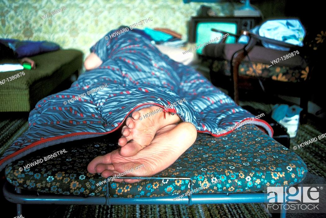 Stock Photo: close up of the bare feet of a sleeper in a camp bed in the spare room.