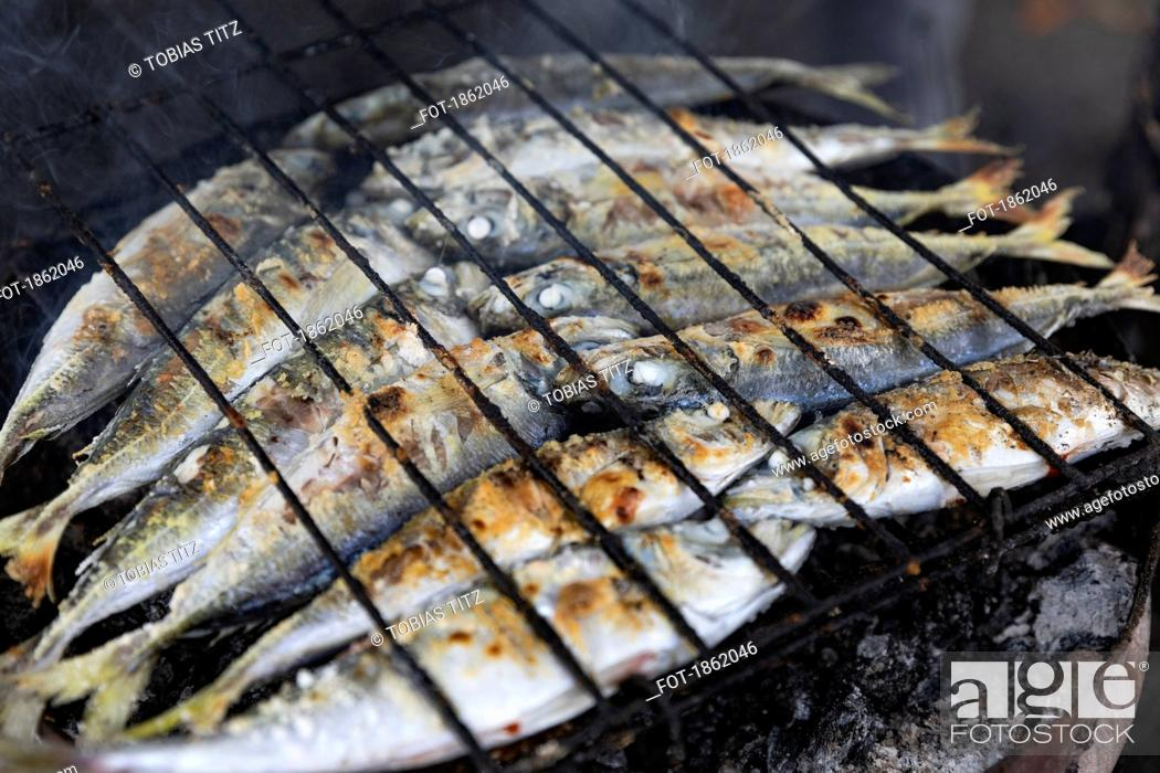 Stock Photo: Whole sardines cooking on barbecue grill.