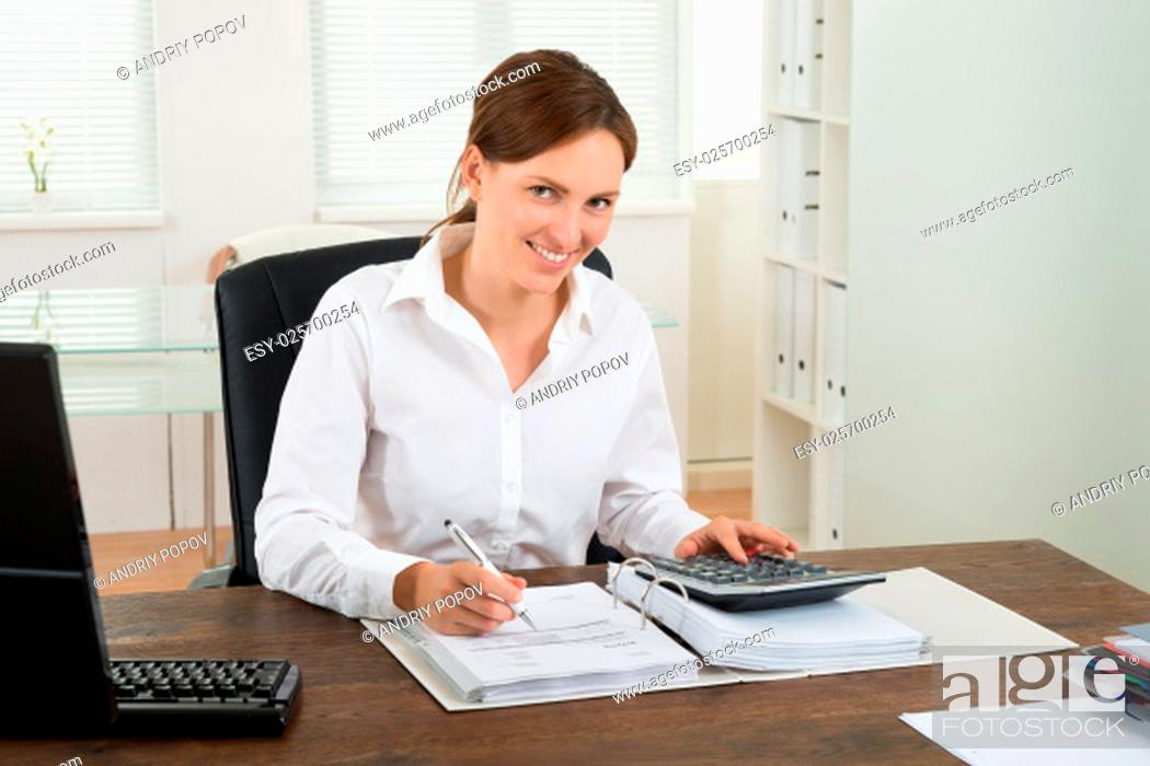 Stock Photo: Photo Of Happy Businesswoman Calculating Invoice At Desk.