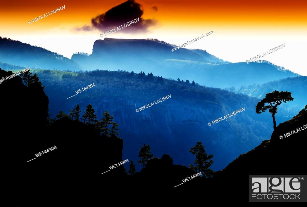 Stock Photo: Horizontal vdramatic mountain trees on rocks silhouette sunset background backdrop.