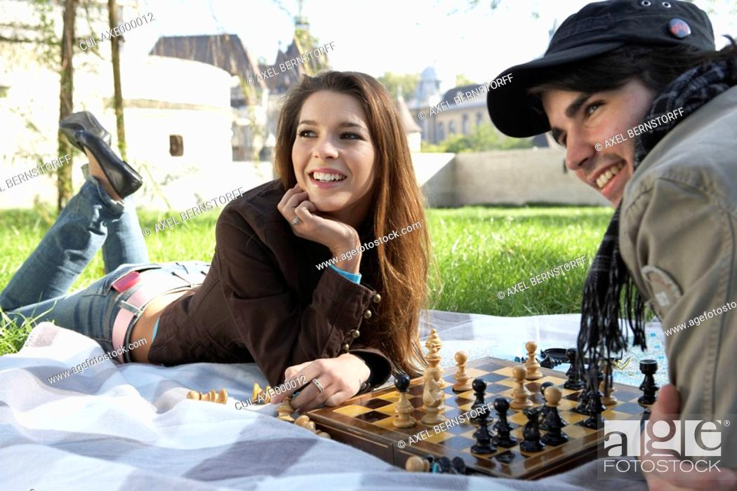 Stock Photo: Couple playing chess in a park smiling.