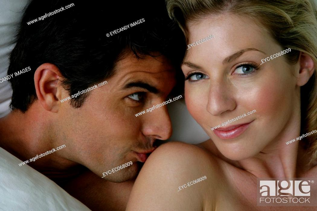 Stock Photo: Young man kissing woman's shoulder in bed.
