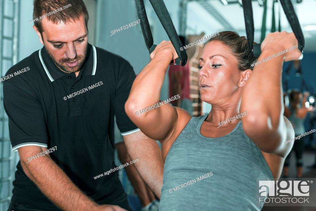 Stock Photo: Woman doing TRX workout with personal trainer.