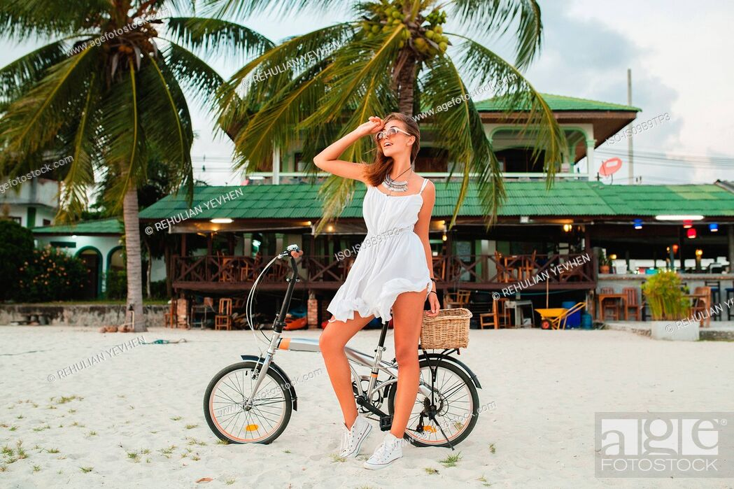 Stock Photo: Young woman with bicycle looking away on sandy beach, Krabi, Thailand.