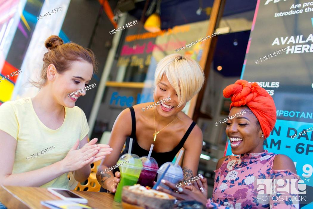 Stock Photo: Young women friends enjoying smoothies at sidewalk cafe.