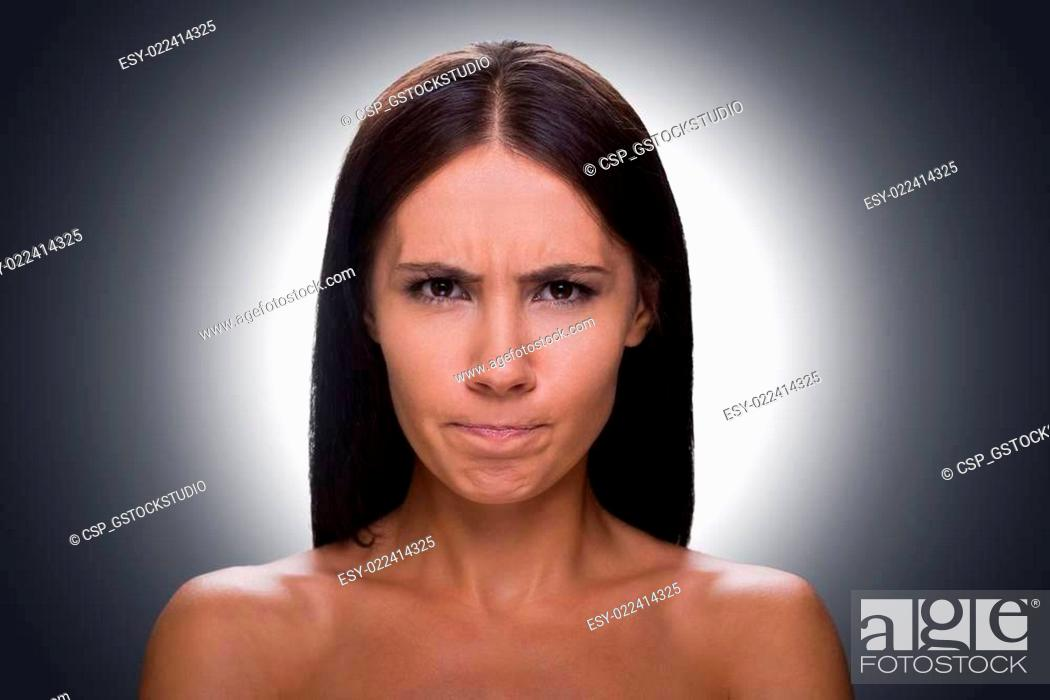 Stock Photo: Woman grimacing. Portrait of young shirtless woman looking at camera and grimacing while standing against grey background.