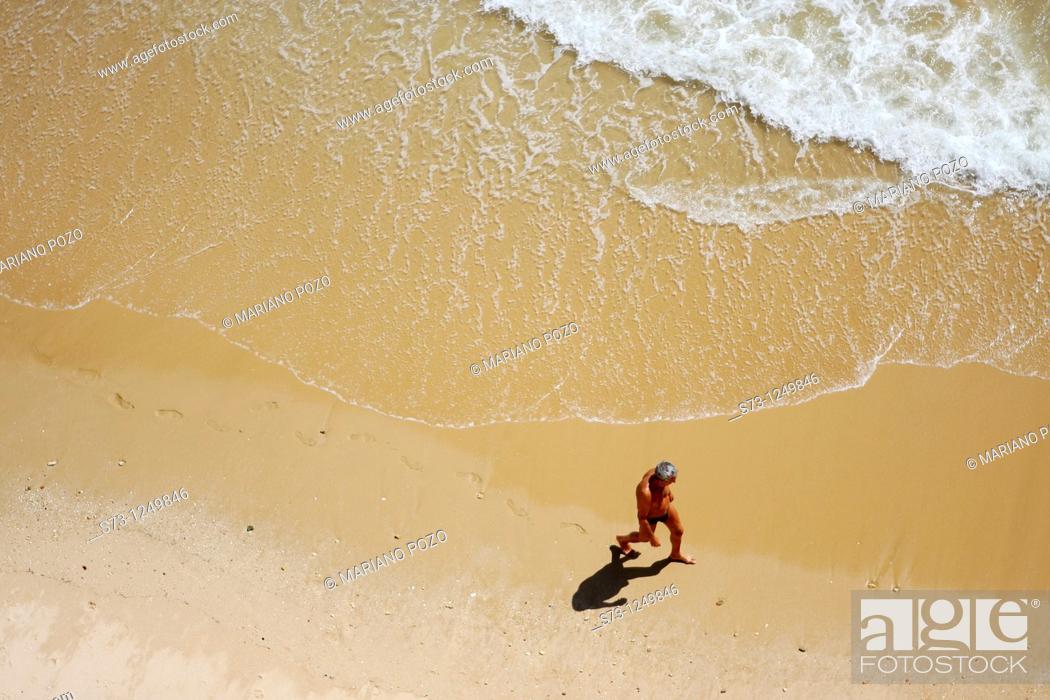Stock Photo: Man lying in Albufeira beach, Algarve, Portugal.