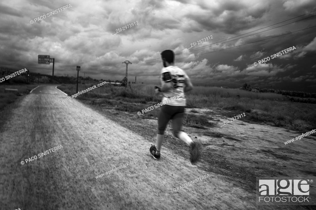 Stock Photo: Man running with storm clouds in background. Alcocebre, Valencian Community, Spain.