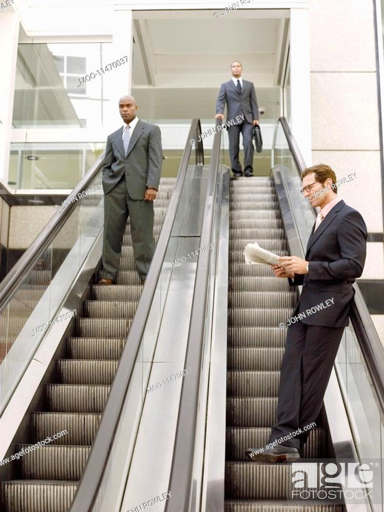 Stock Photo: Businessmen on escalators.