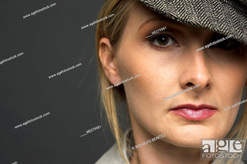 Stock Photo: Blond woman with hat posing in the studio.