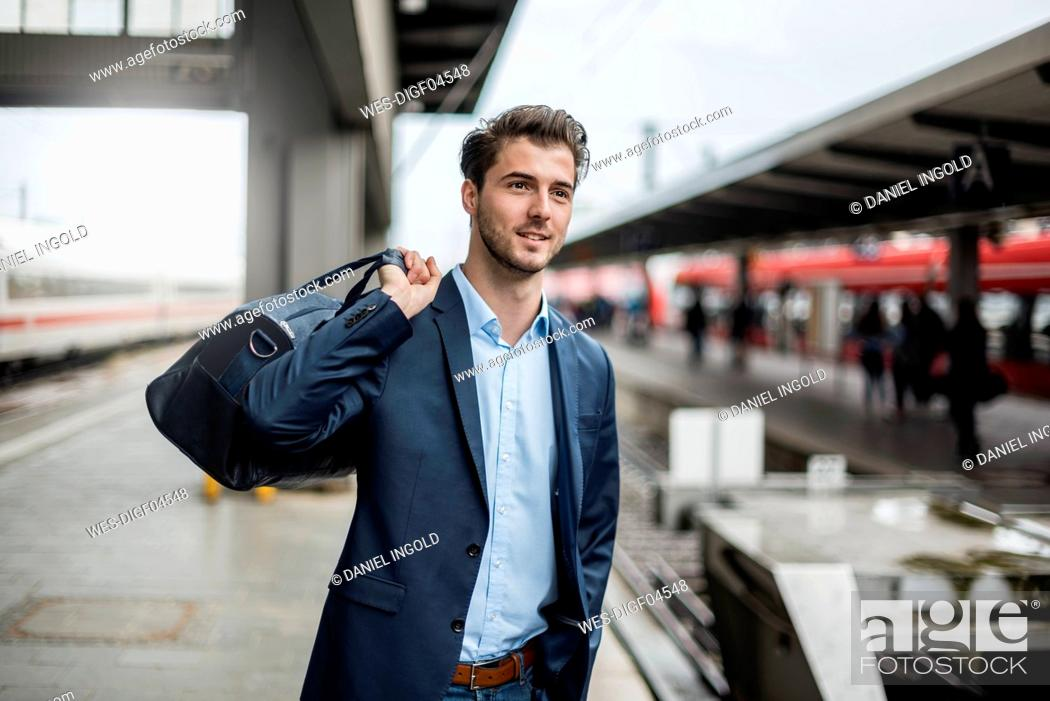 Stock Photo: Smiling businessman with bag at the platform.