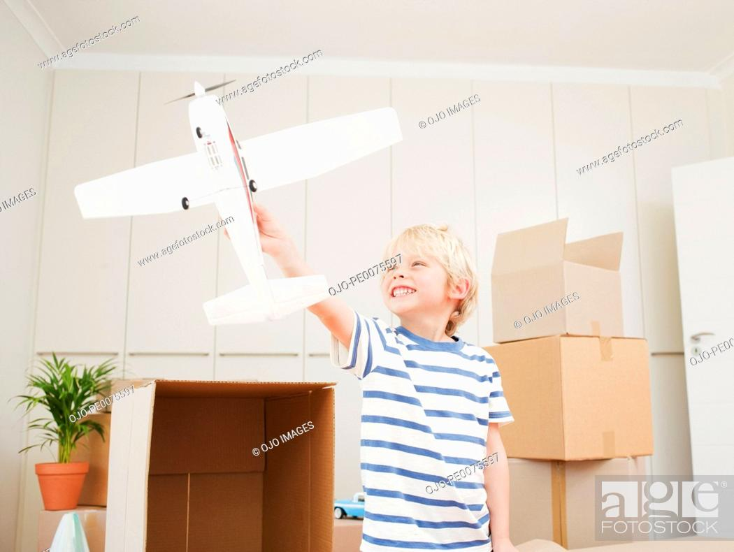 Stock Photo: Boy playing with model airplane in new house.