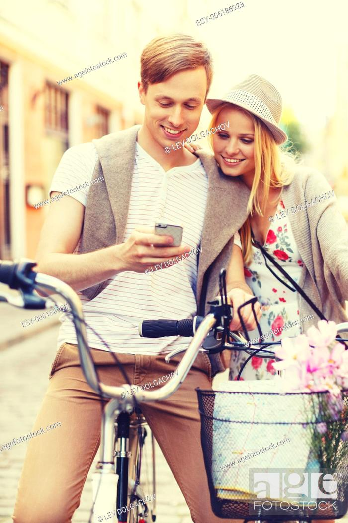 Imagen: summer holidays, love, navigation, gps and dating concept - couple with bicycles and smartphone in the city.