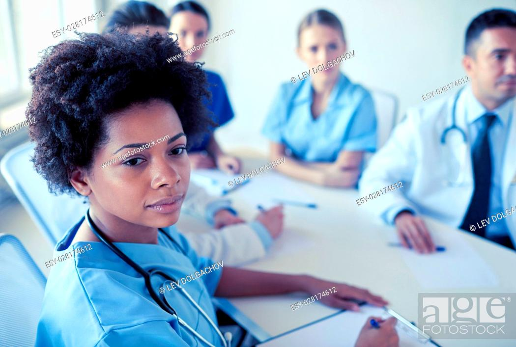 Stock Photo: health care, profession, people and medicine concept - african american female doctor or nurse over group of medics meeting at hospital.