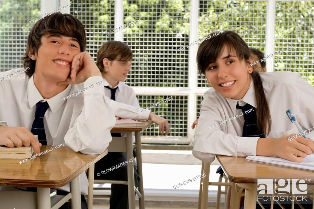 Stock Photo: Teenage girl and a young man sitting in a classroom and smiling.