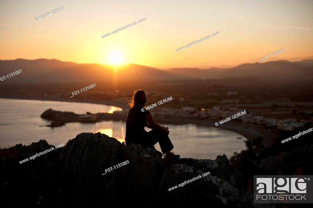 Stock Photo: A silhouetted person sitting atop a hill watching the sunset, Rhodes, Greece.