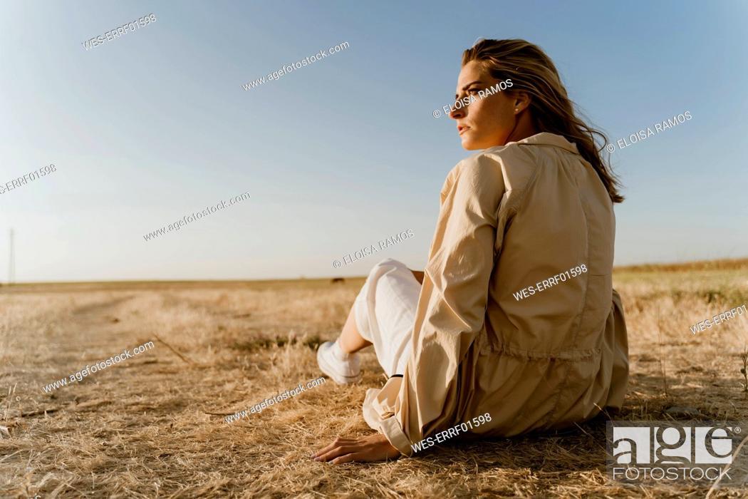Stock Photo: Female traveller sitting on dry meadow, looking sideways.