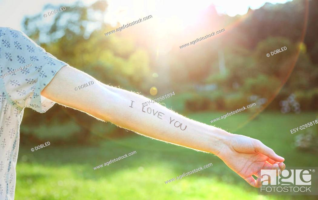Stock Photo: Closeup of male arm with the text -I love you- written in the skin over a sunny nature background.