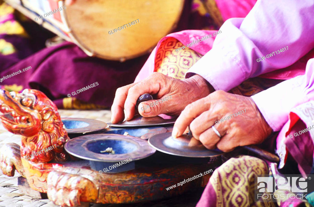 Stock Photo: Mid section view of a person playing cymbals, Bali, Indonesia.