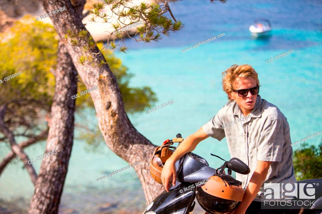 Stock Photo: Young man sitting on moped at coast, Majorca, Spain.