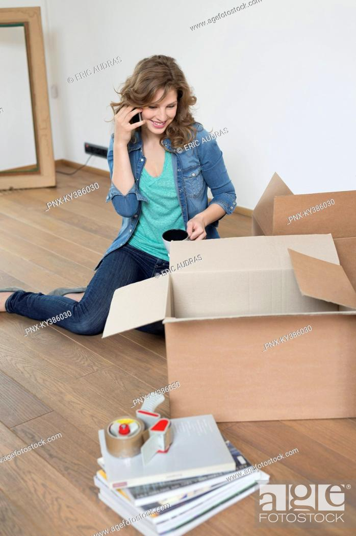Stock Photo: Woman talking on a mobile phone near cardboard boxes.