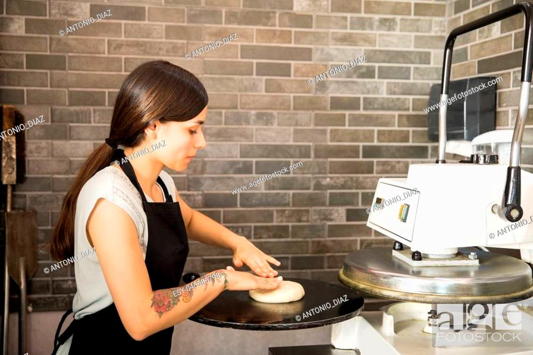 Stock Photo: Busy woman wearing black apron concentrating on keeping dough on press machine to make pizza bread in kitchen at pizza shop.