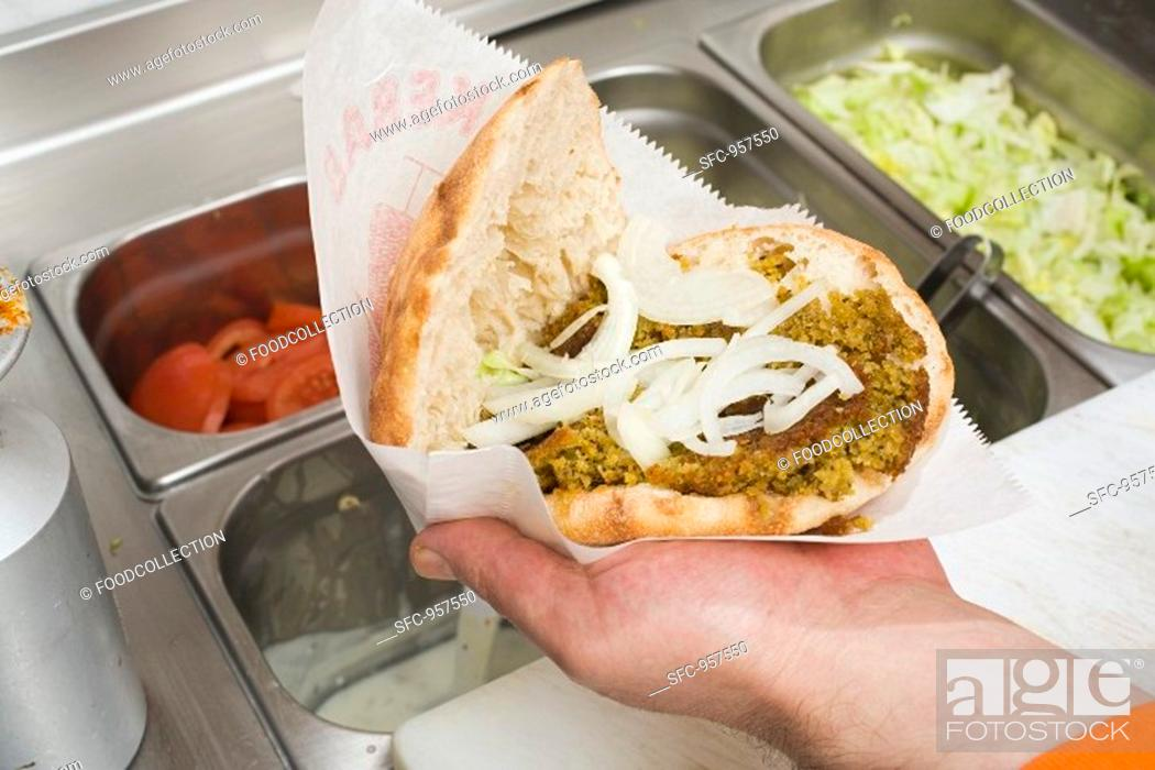 Stock Photo: Hand holding opened döner kebab with onions.