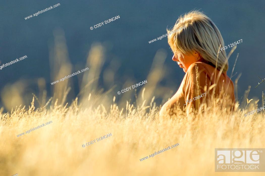 Stock Photo: Blond female sitting in golden autumn grass in Arthur's Pass, New Zealand.