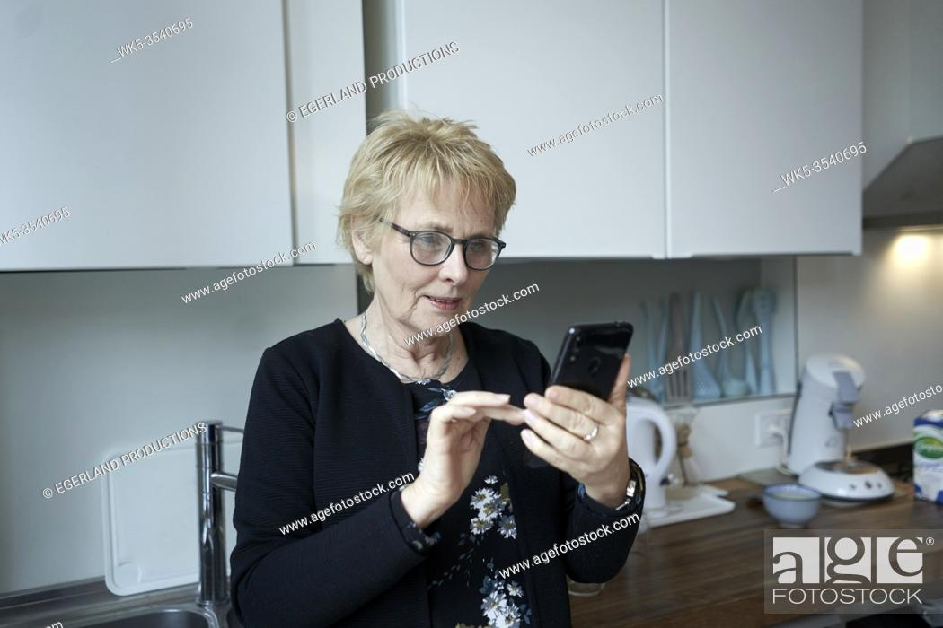Stock Photo: senior woman using smartphone at breakfast table in kitchen.