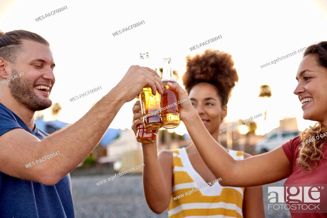 Stock Photo: Three friends toasting with beer bottles on the beach at sunset.