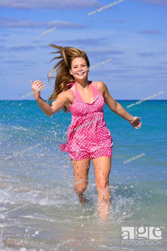 Stock Photo: Beautiful Caucasian female teenage running through to surf wearing a colorful bikini.