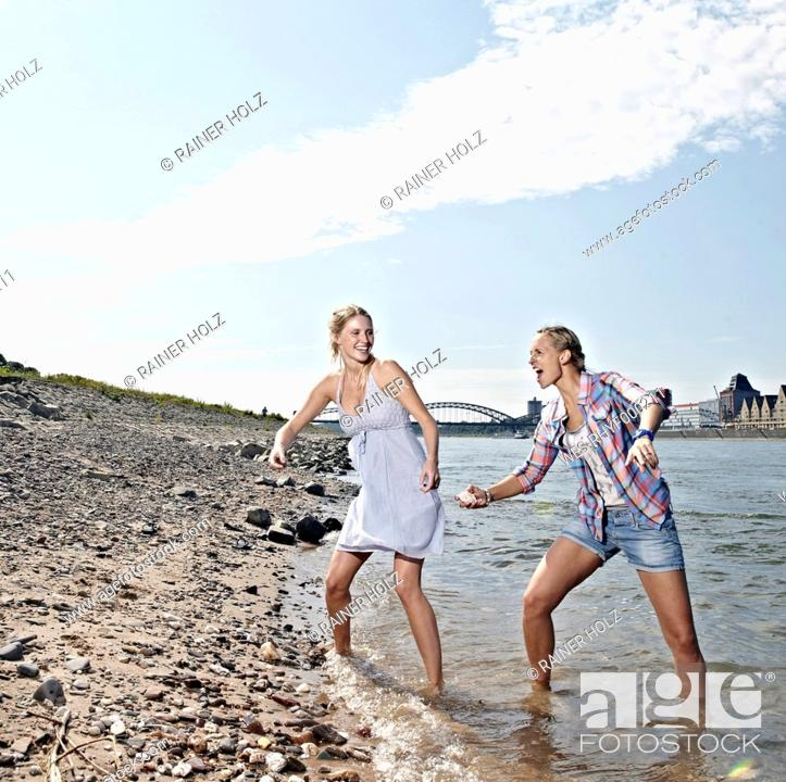 Stock Photo: Germany, Cologne, Young women skipping stones in river.