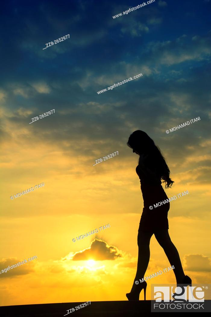 Stock Photo: Full length woman's silhouette walking against a dramatic sunset.