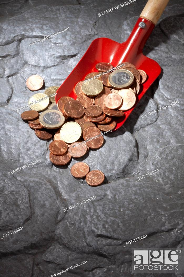 Stock Photo: A red shovel with a heap of Euro coins.