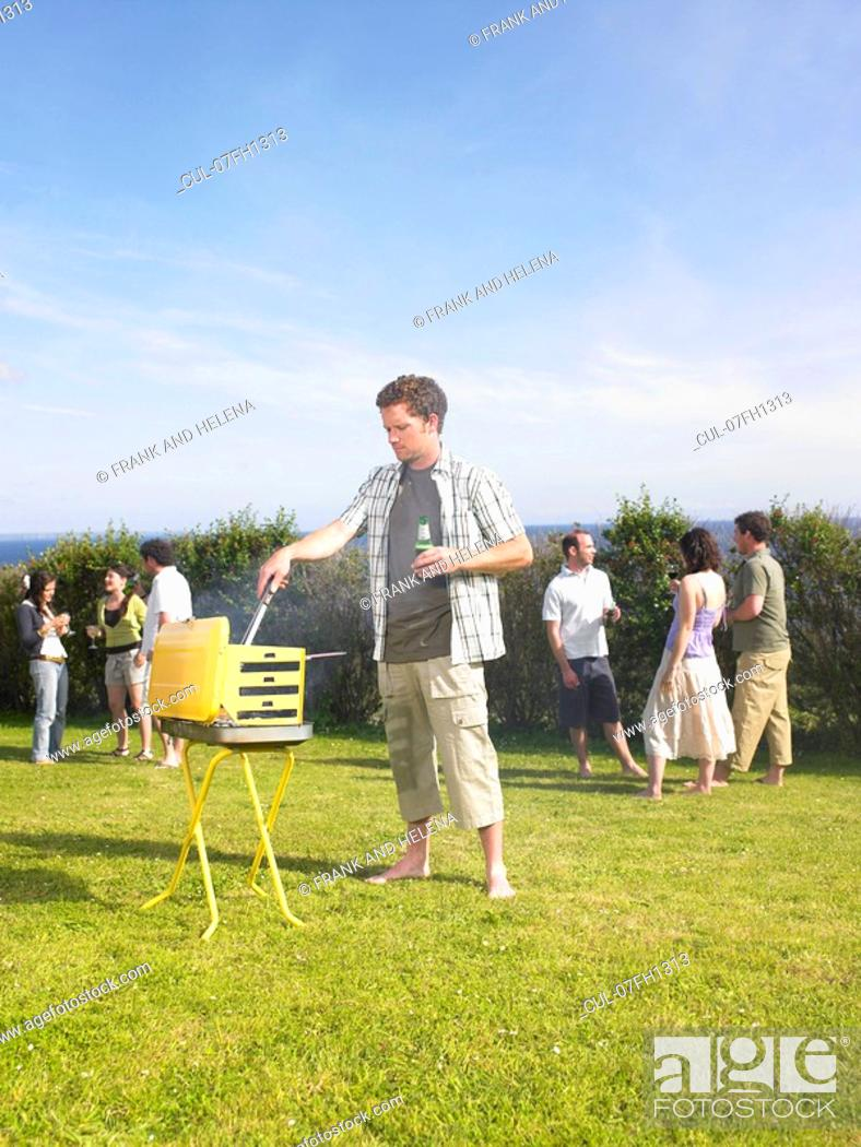 Stock Photo: Man tending barbecue at a party.
