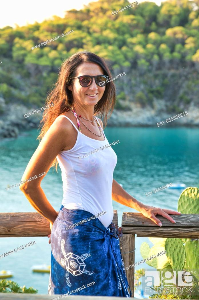 Stock Photo: Woman relaxing at the sea, ocean in background, front view.