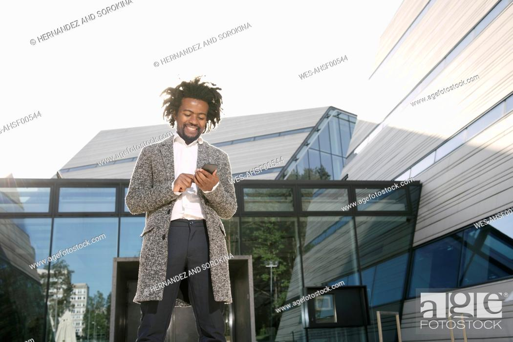 Imagen: Smiling businessman using cell phone outside office.