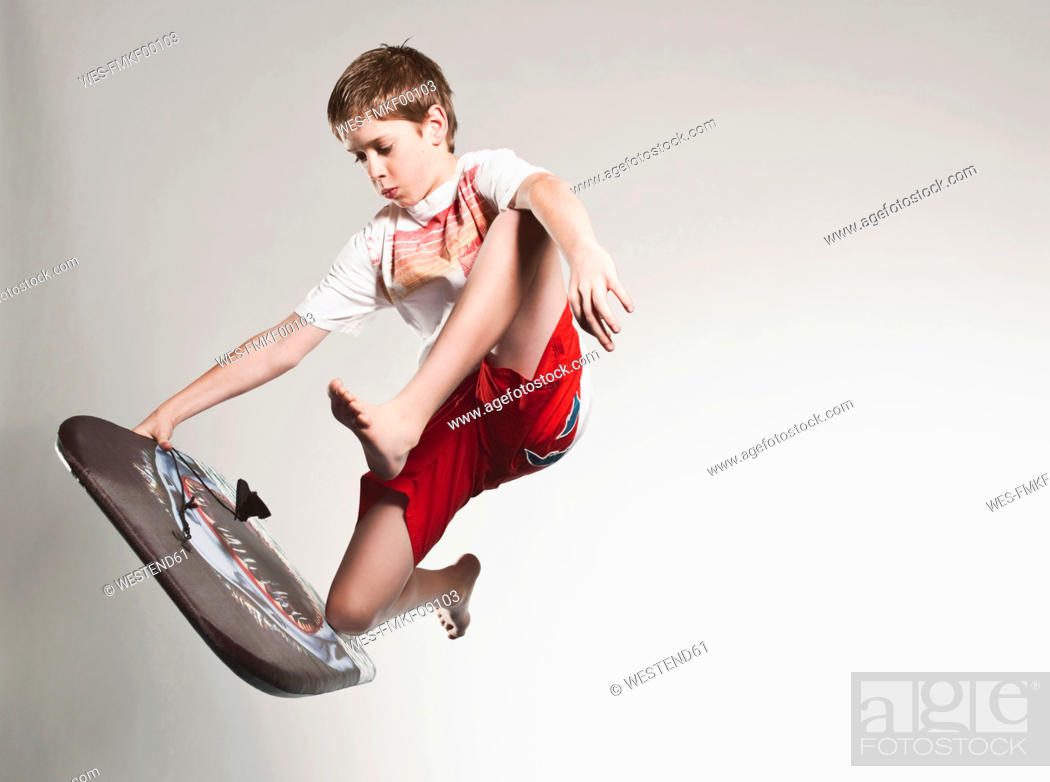 Stock Photo: Boy 12-13 jumping with boogie board.