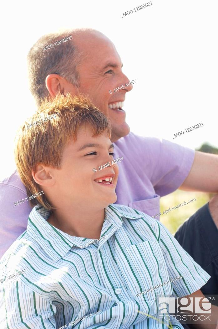 Stock Photo: Father and Son sitting on beach looking at view portrait.