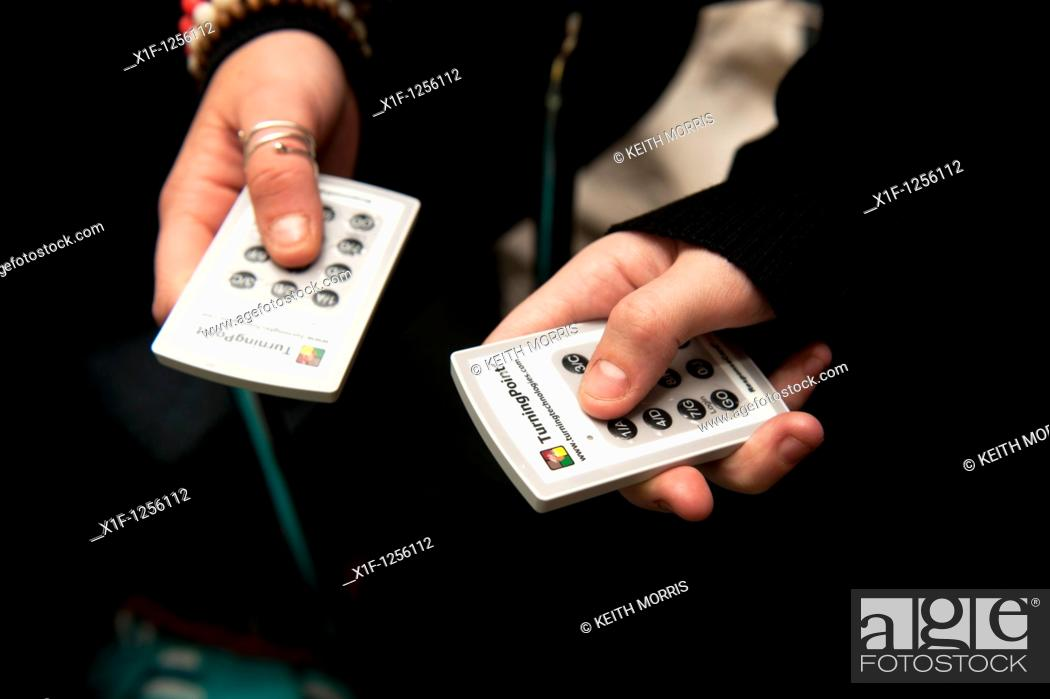 Stock Photo: Using TurningPoint interactive response electronic infrared IR voting handsets, UK.