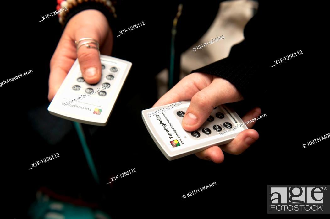 Stock Photo: Using TurningPoint interactive response electronic infrared IR voting handsets, UK.