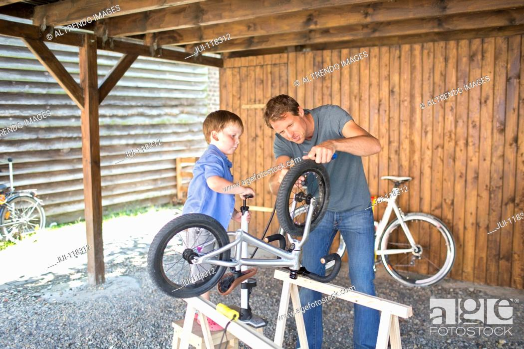 Imagen: Father And Son Mending Bicycle In Garage At Home.