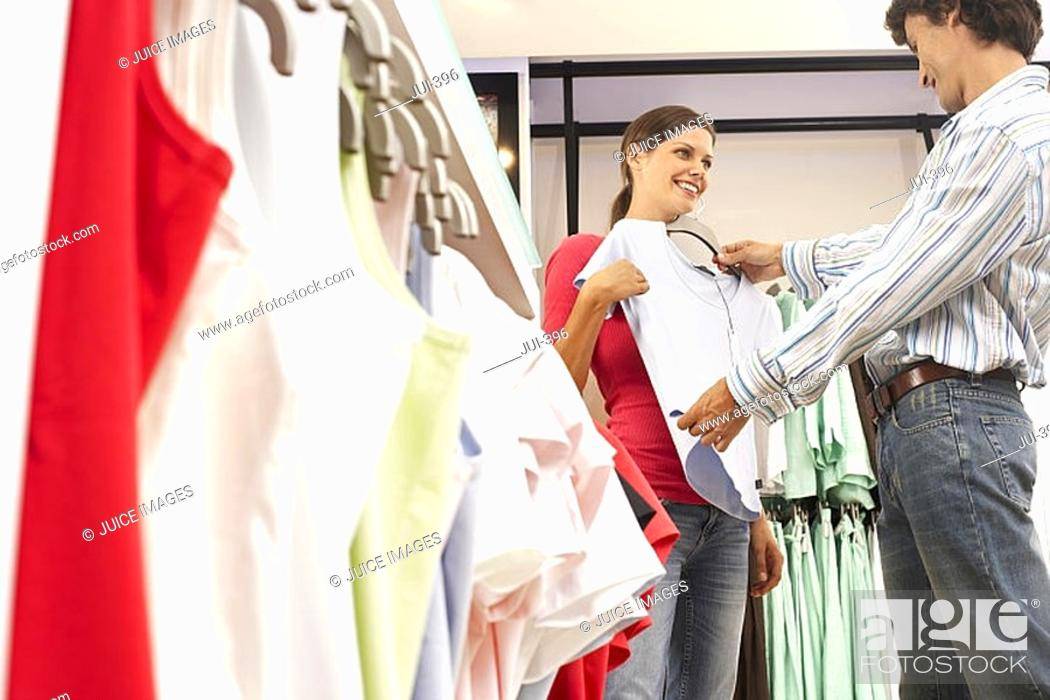 Stock Photo: Couple shopping in clothes shop, man holding pale blue top up against girlfriend, smiling, side view.