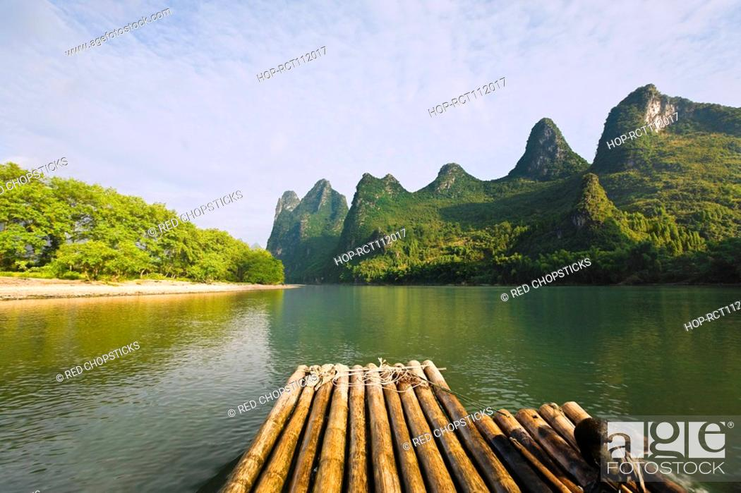 Stock Photo: Bamboo raft in a river with a hill range in the background, Guilin Hills, XingPing, Yangshuo, Guangxi Province, China.