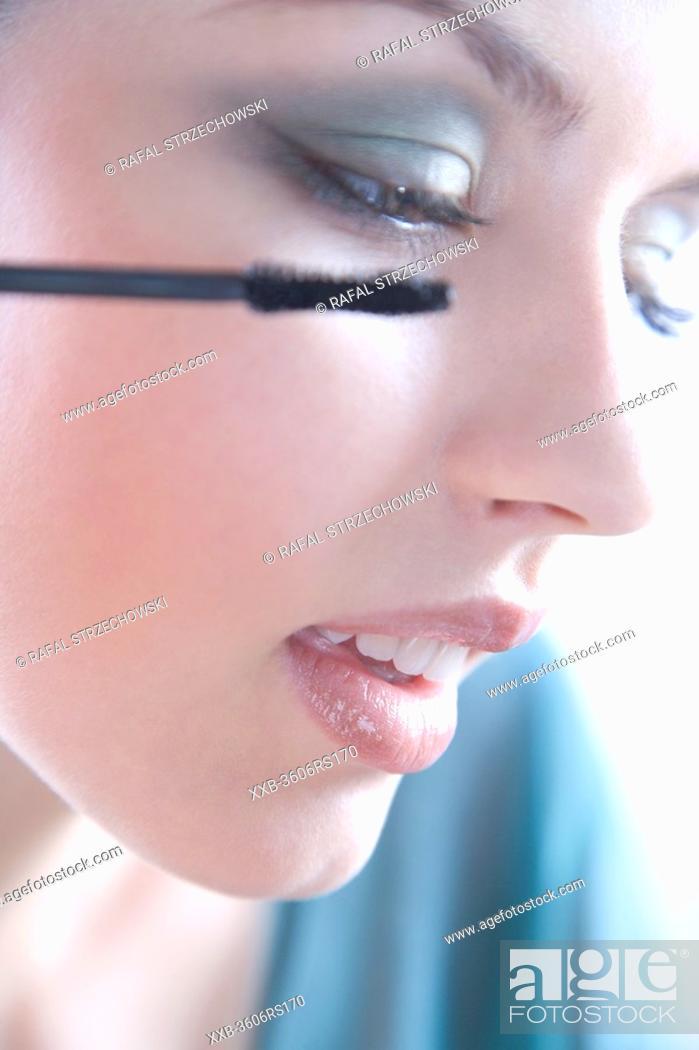 Stock Photo: woman using mascara.