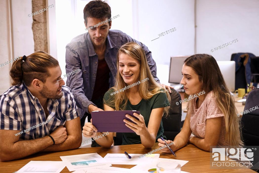Stock Photo: Young professional team with two males and two females planning a fresh new approach for their company to evolve further and better with tablet pc.