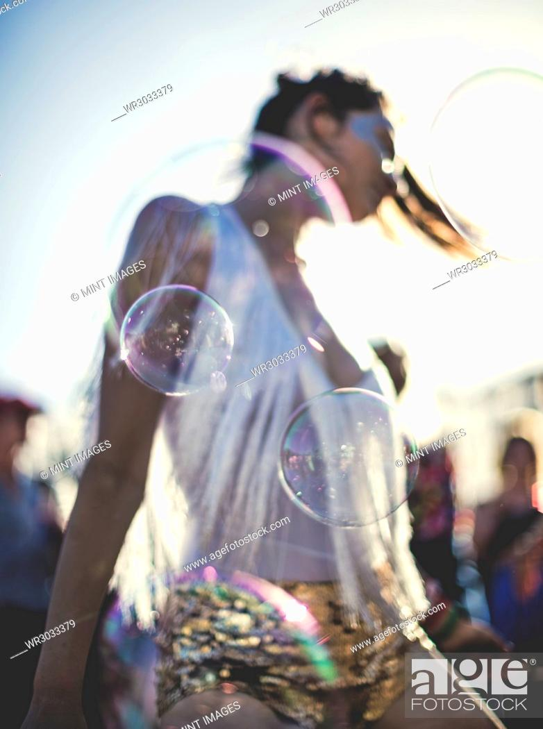 Imagen: Young woman at a summer music festival wearing golden sequinned hot pants, dancing among the crowd.