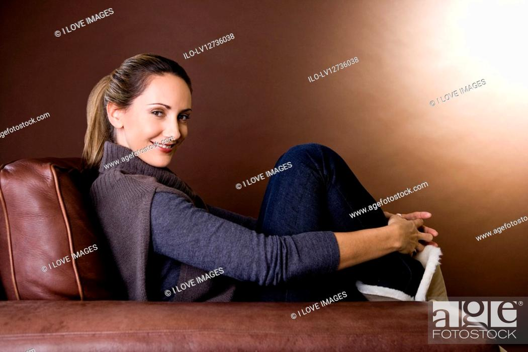 Stock Photo: A mid adult woman relaxing in an armchair.