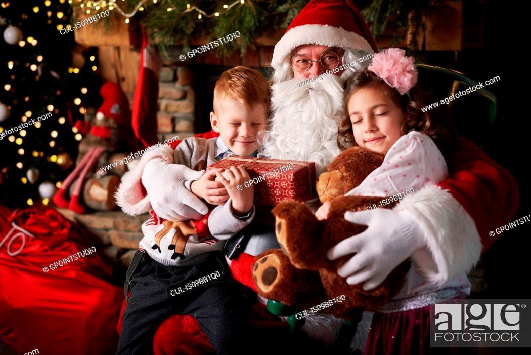 Stock Photo: Young girl and boy visiting Santa, holding gifts.